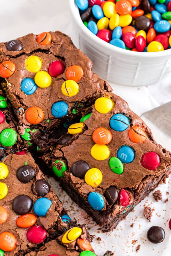 M&M brownies cut into squares with bowl of candies in background.