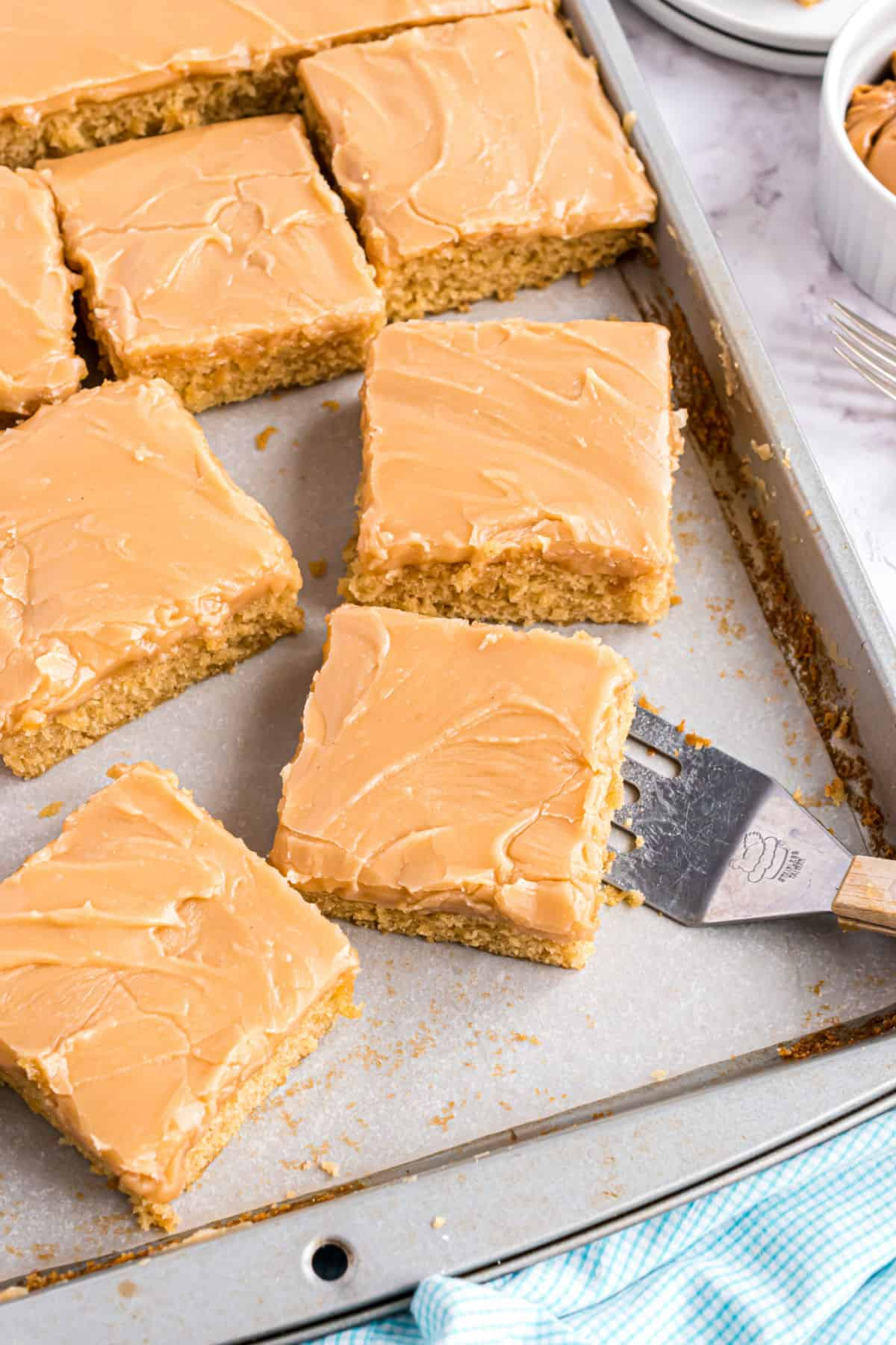 Peanut butter sheet cake sliced into squares on a baking sheet.
