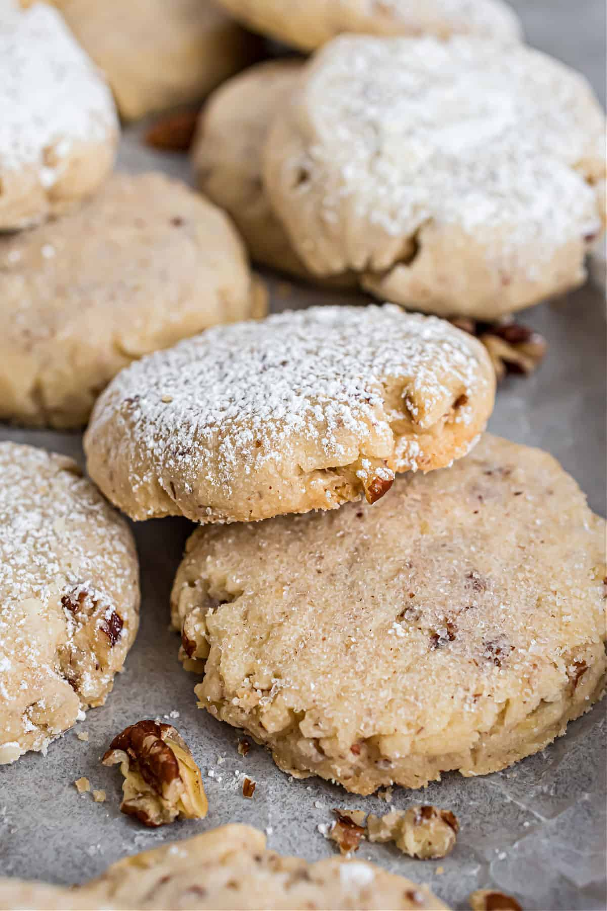 Pecan sandies on cookie sheet, some dusted with powdered sugar.
