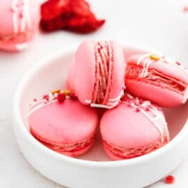Strawberry macarons in a white bowl.