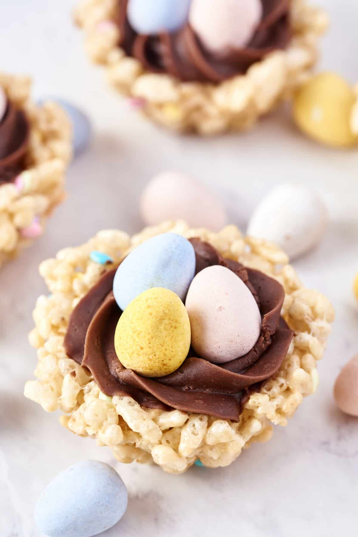 Rice krispie treats shaped as a nest and filled with chocolate frosting and candy.