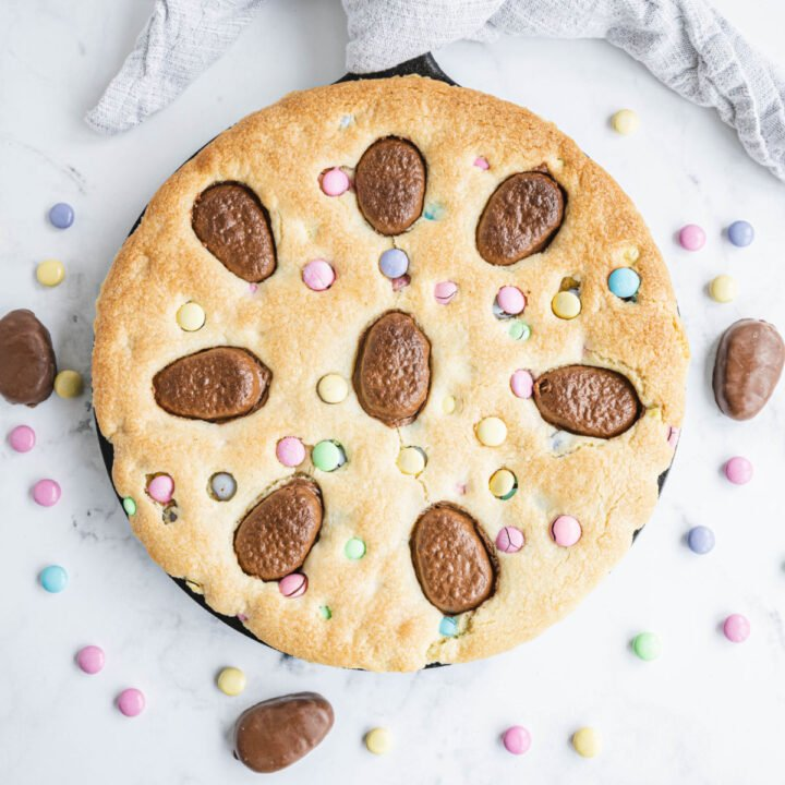 This Sugar Cookie Cake has everything you love about your favorite cut out treats, only it's baked as one GIANT cookie the size of a cake. M&Ms and peanut butter cups make this cookie cake even better. Perfect for holidays and only 5 ingredients!