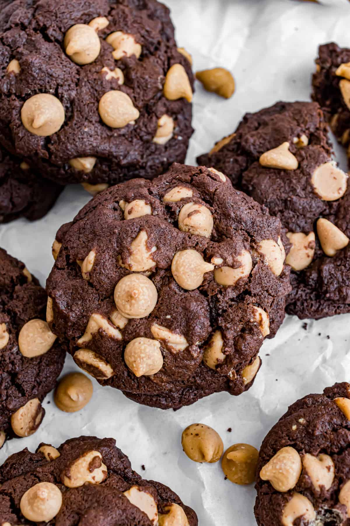 Chocolate peanut butter cookies stacked on parcment paper.