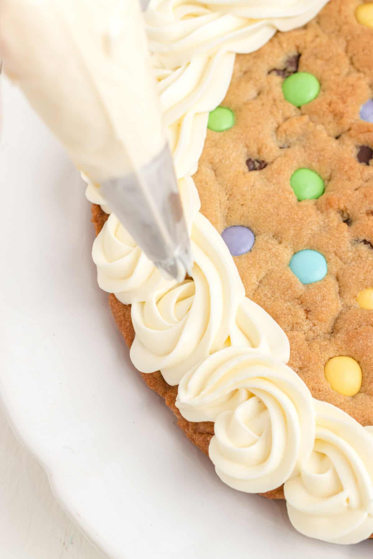 Sugar cookie frosting being piped onto an Easter cookie cake.