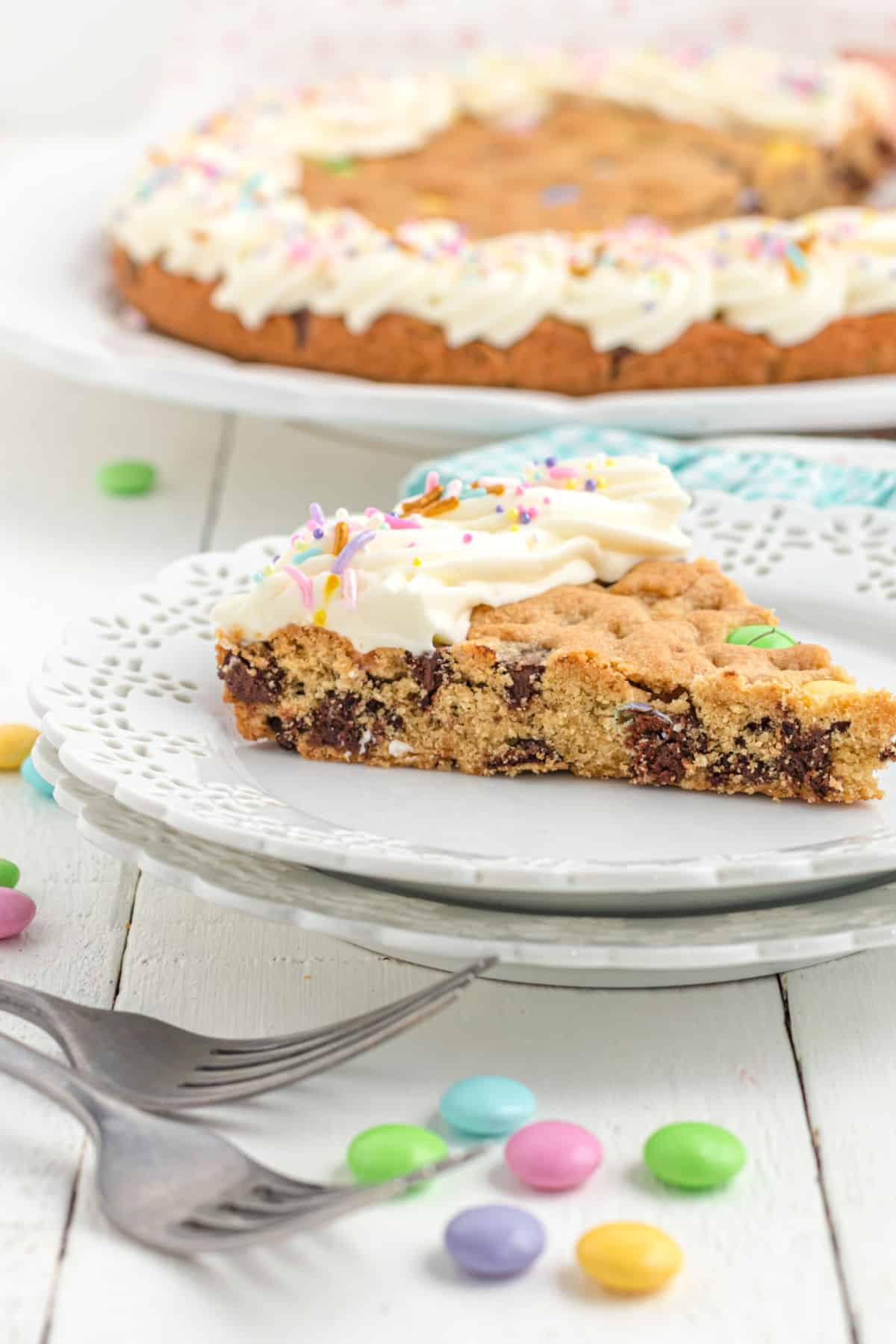 Slice of chocolate chip cookie cake on a white plate.