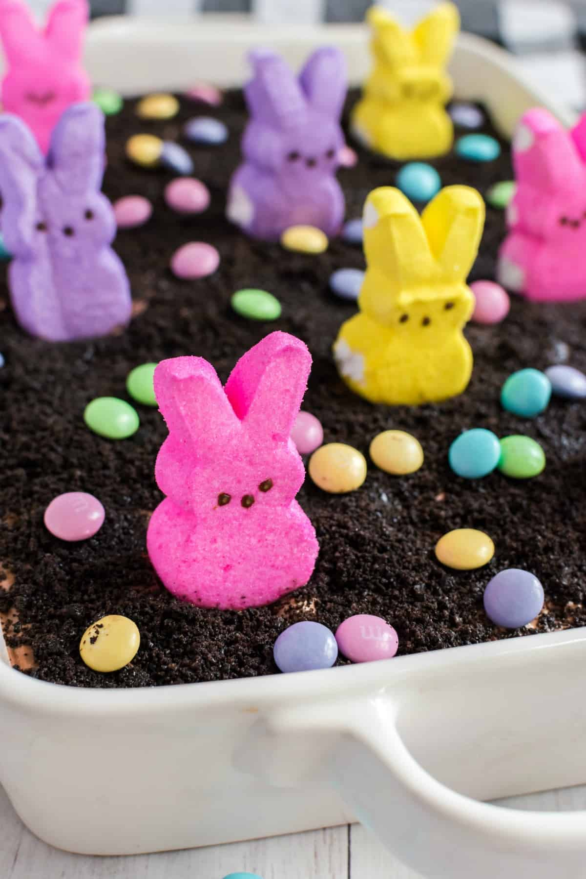 Easter dirt pudding cake topped with pasted M&M's and PEEPS marshmallows.