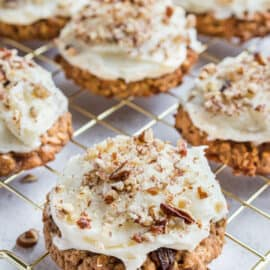 Cream cheese frosted carrot cake cookies on wire rack.