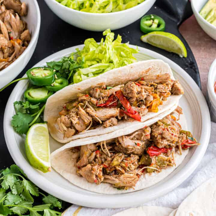 Chicken fajitas on flour tortillas with toppings on side.