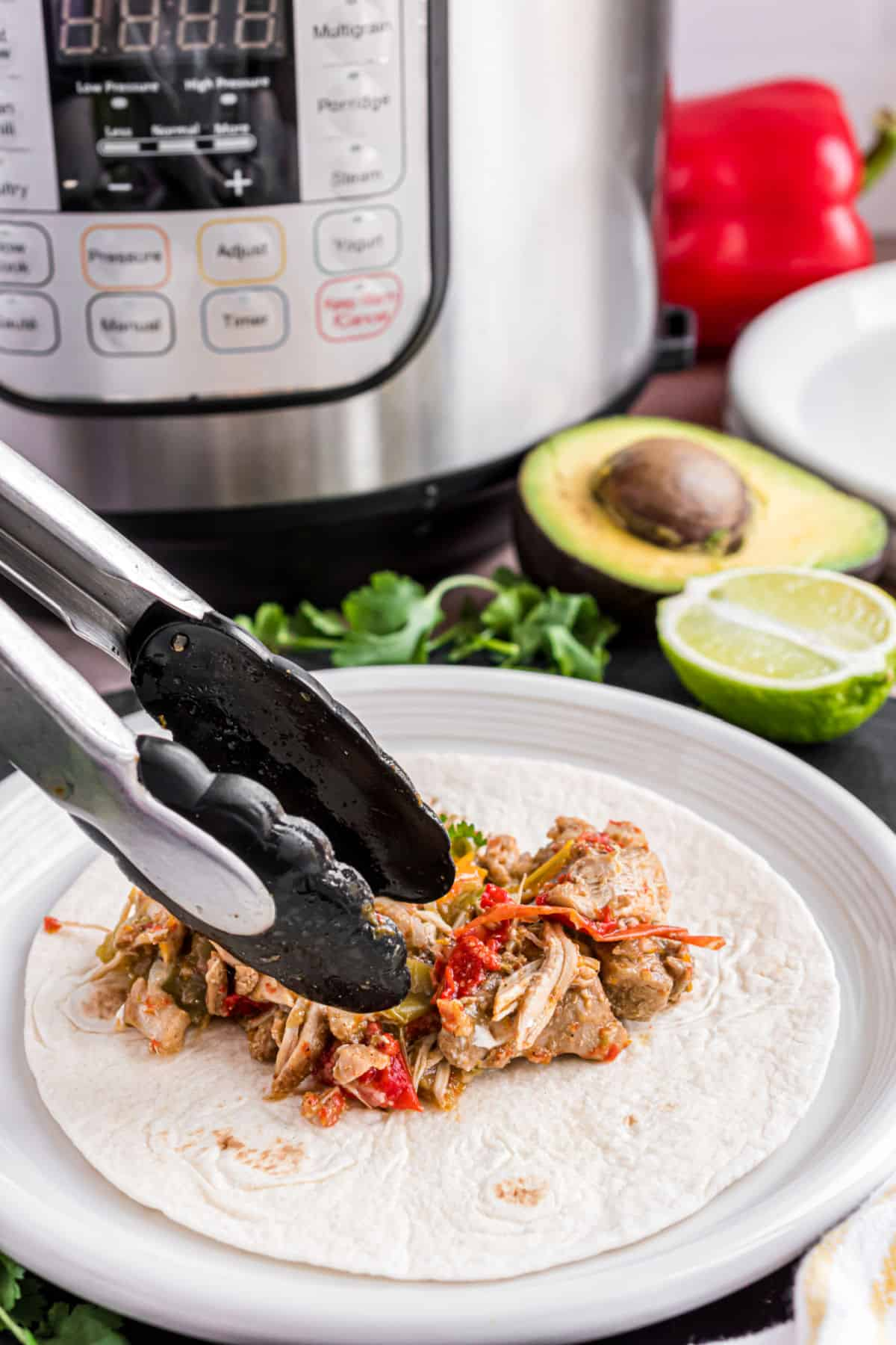 Chicken fajitas made in the Instant Pot being put on a flour tortilla with tongs.