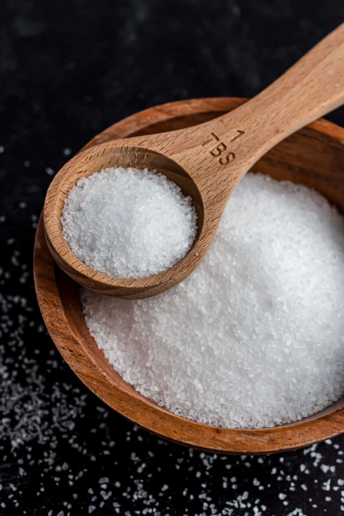 Kosher salt in a wooden bowl with wooden tablespoon.