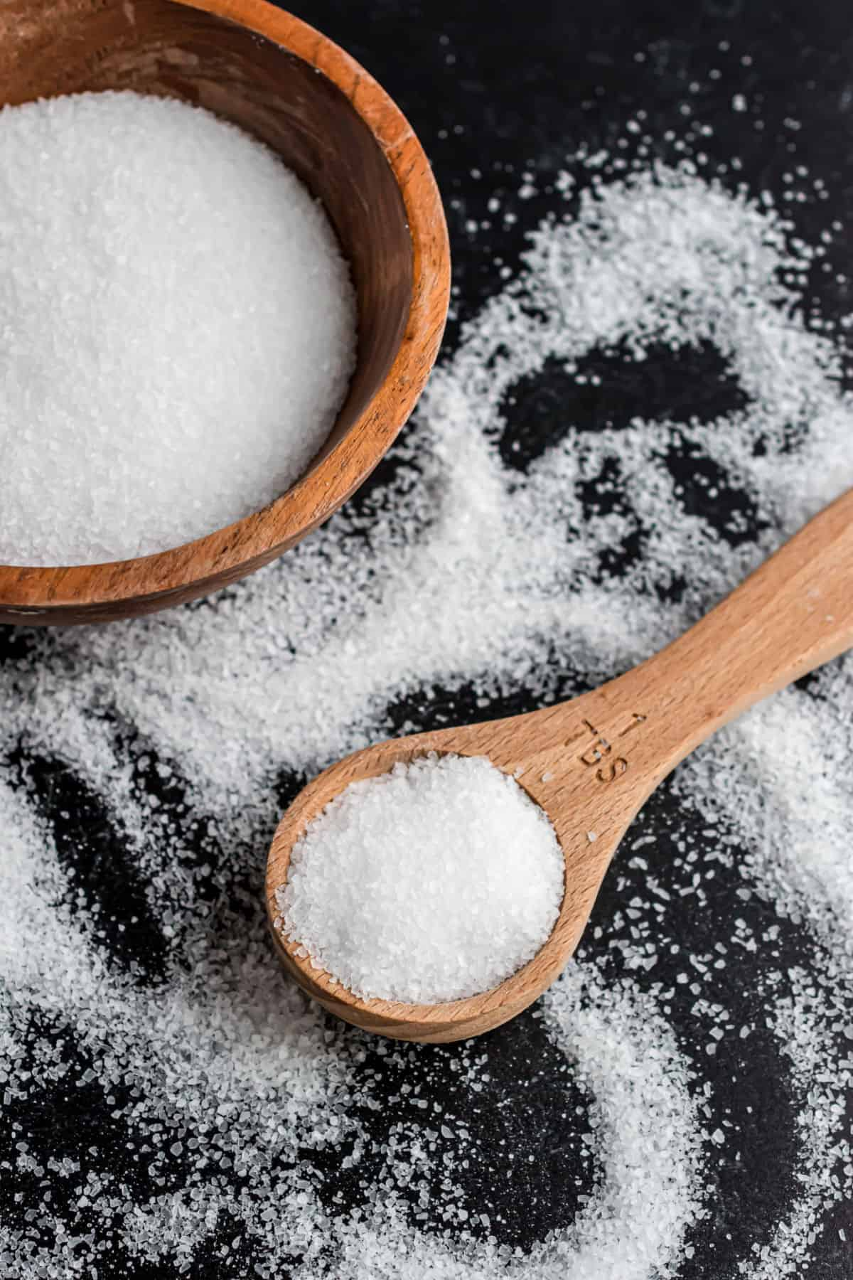 Kosher salt in a wooden bowl spilled onto a balck surface with a wooden spoon.
