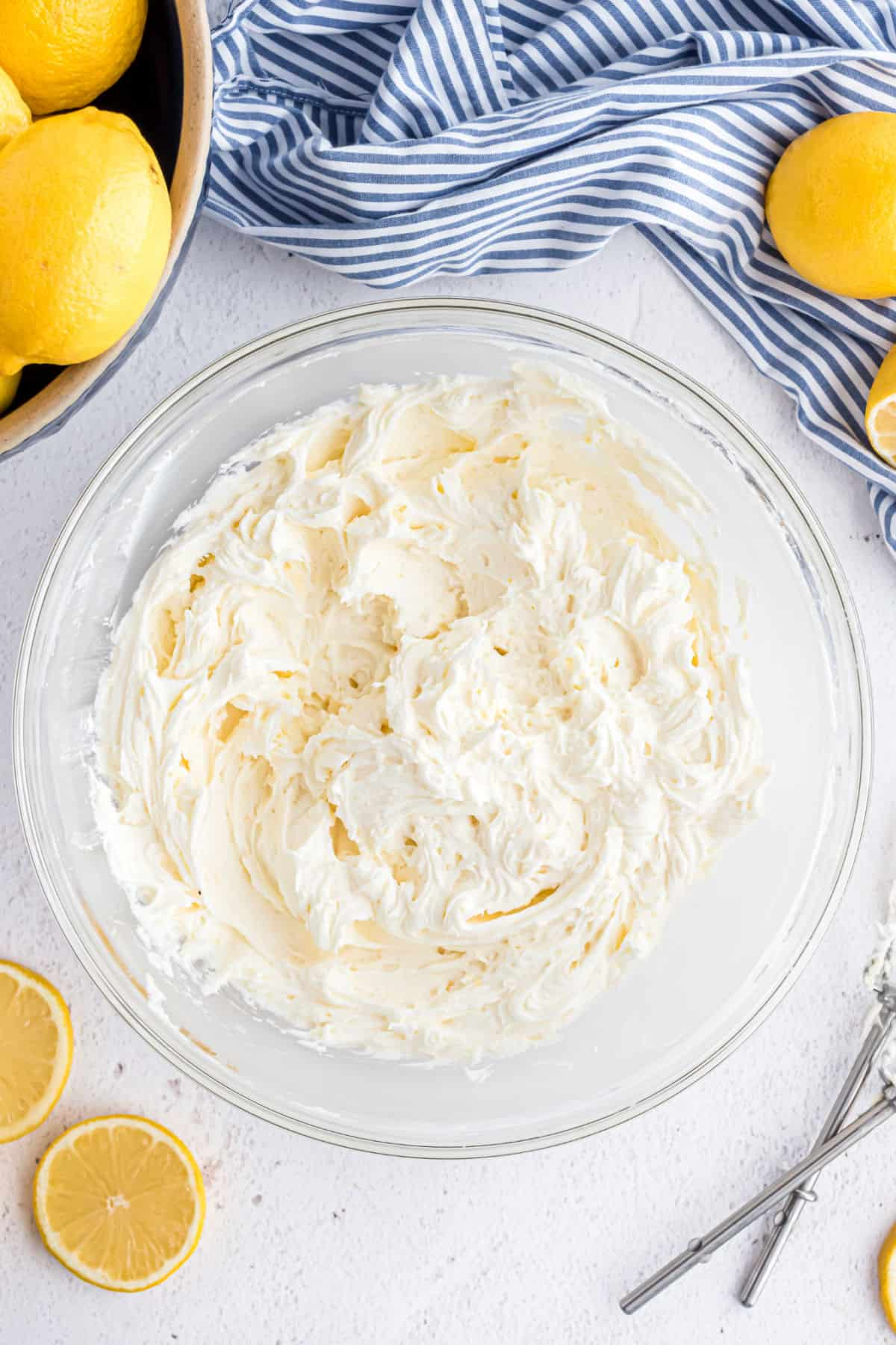 Creamy lemon frosting in a clear glass bowl.
