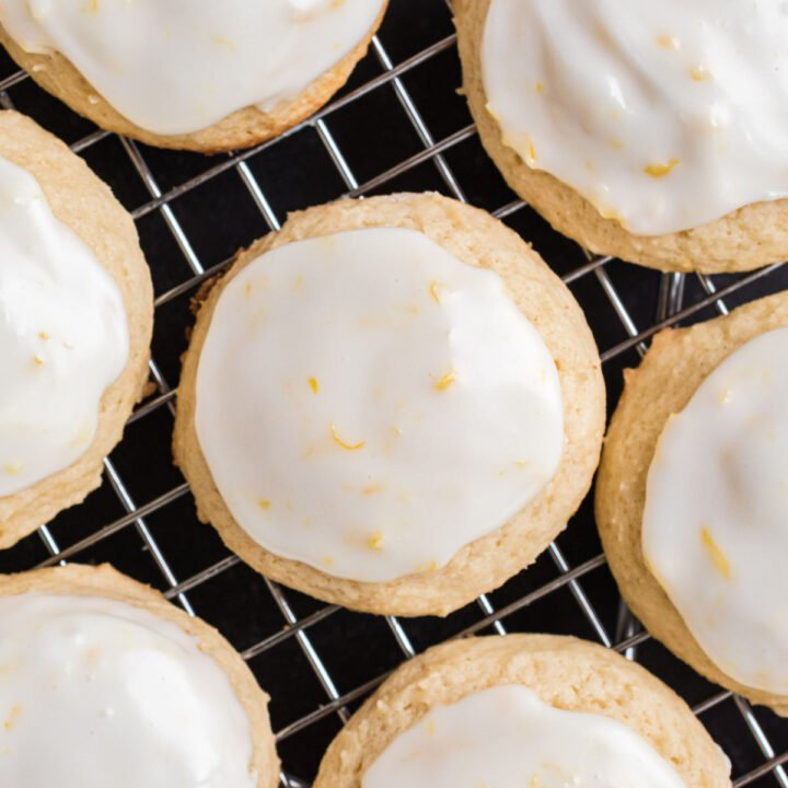 Lemon iced ricotta cookies on a wire cooling rack.