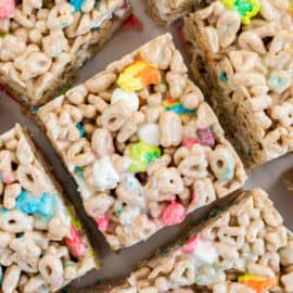Lucky charms marshmallow treat bars cut into squares on parchment paper.