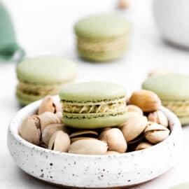 Pistachio macarons on a bowl of pistachios.
