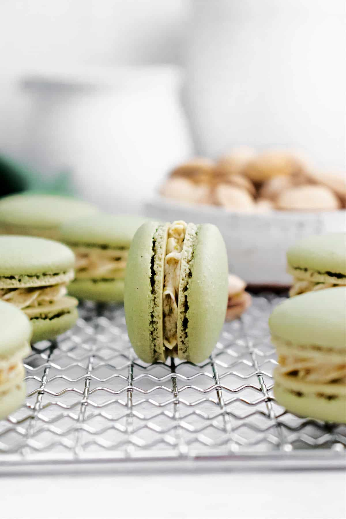 Pistachio macarons on a wire cooling rack.