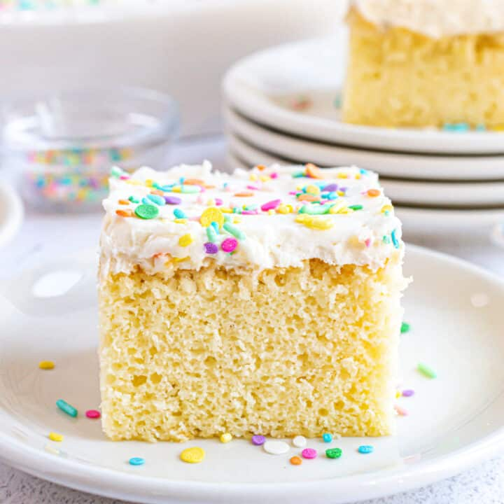 Slice of vanilla cake with vanilla frosting and sprinkles on a white dessert plate.