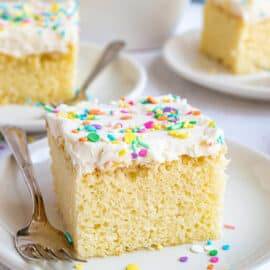 Slice of vanilla cake with vanilla frosting and colorful sprinkles.