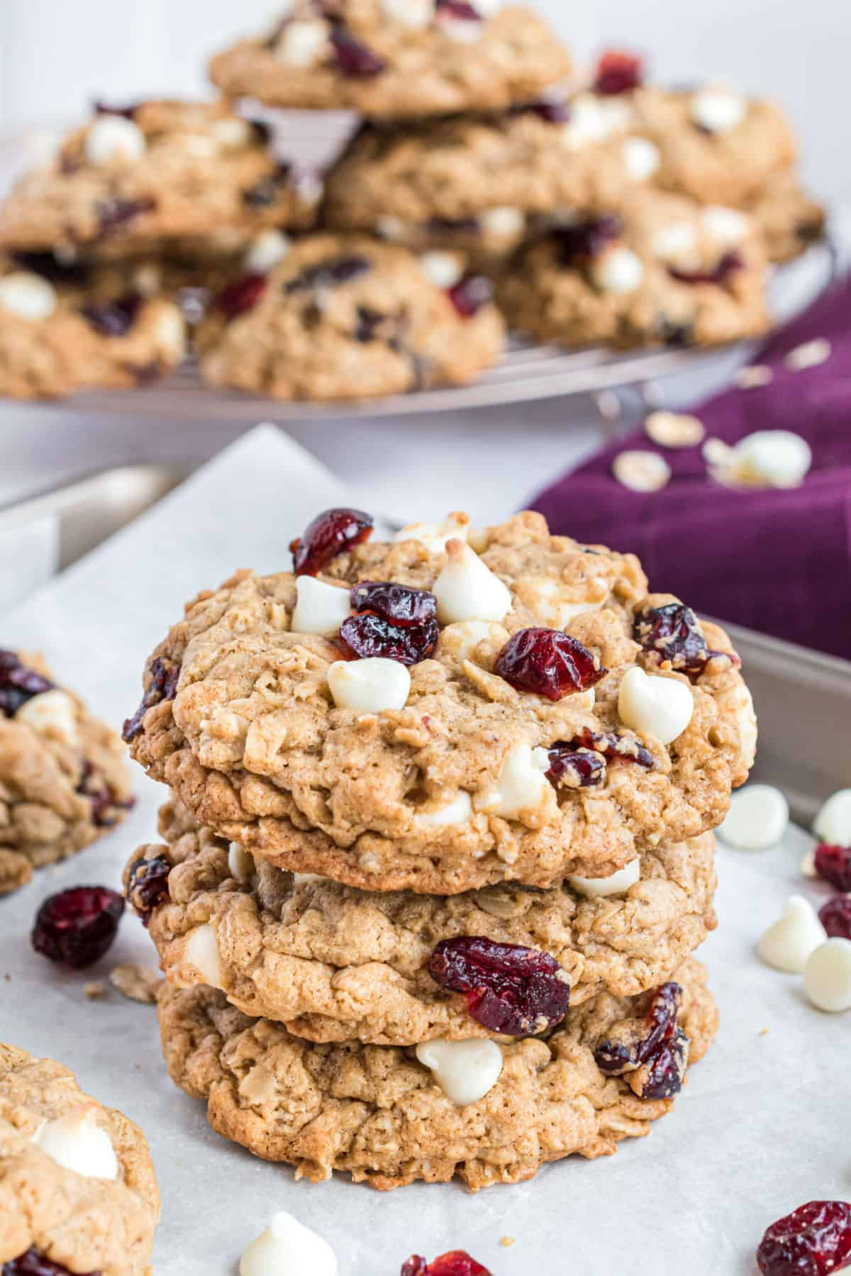 Stack of three oatmeal cookies with white chocolate and craisins.