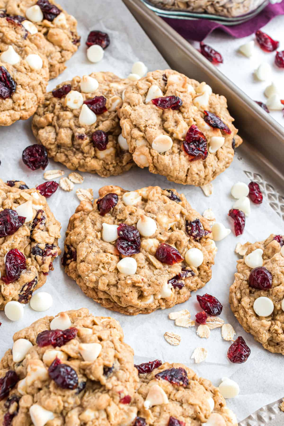 Stacks of white chocolate oatmeal cranberry cookies on a parchment paper lined cookie sheet.