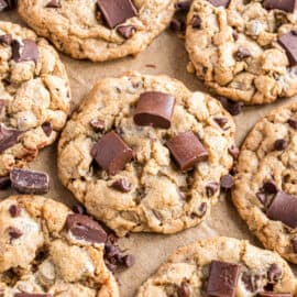 Chocolate chip cookies with chocolate chunks on parchment paper.