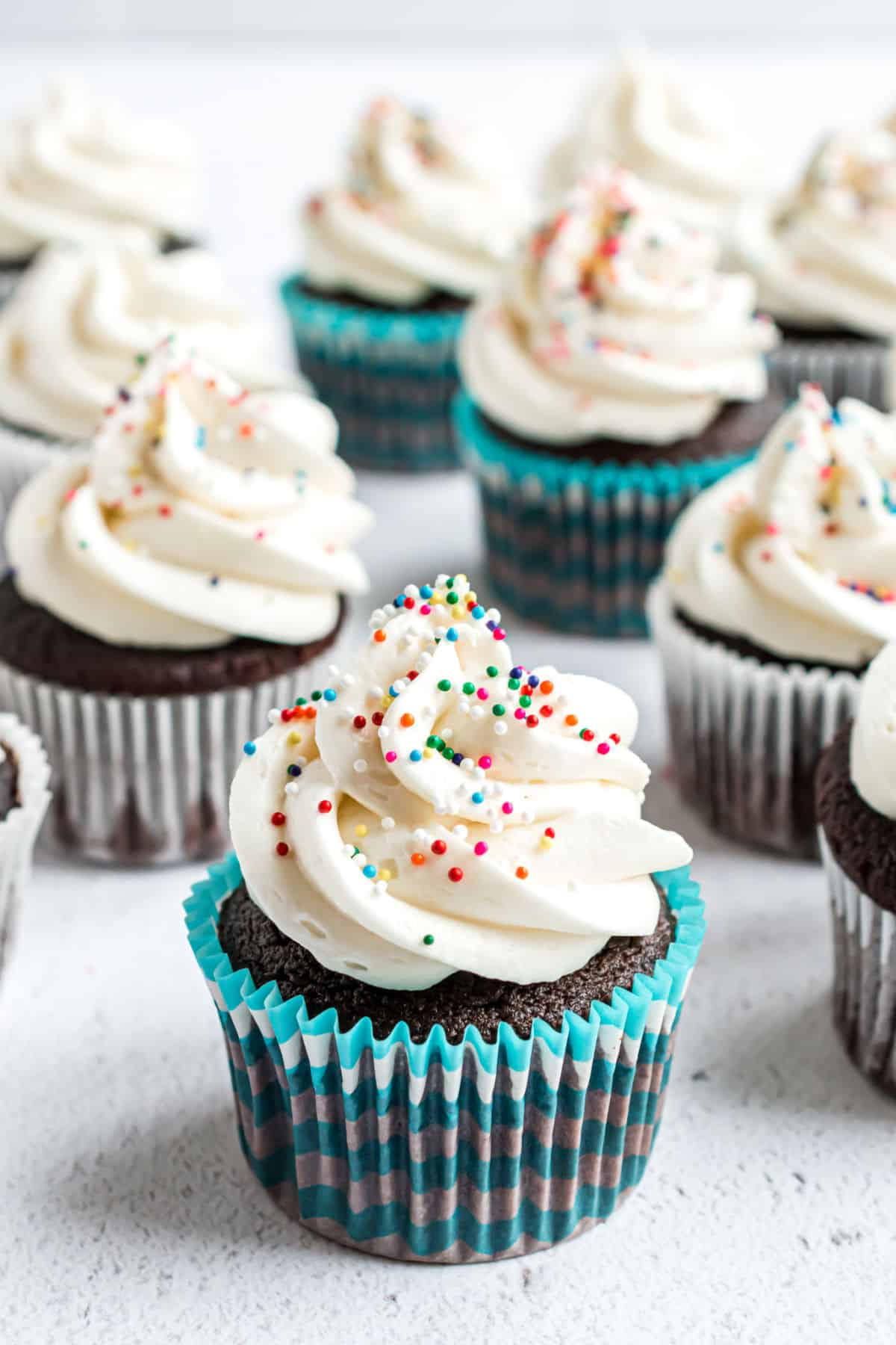 Vanilla buttercream frosting piped onto chocolate cupcakes with sprinkles.