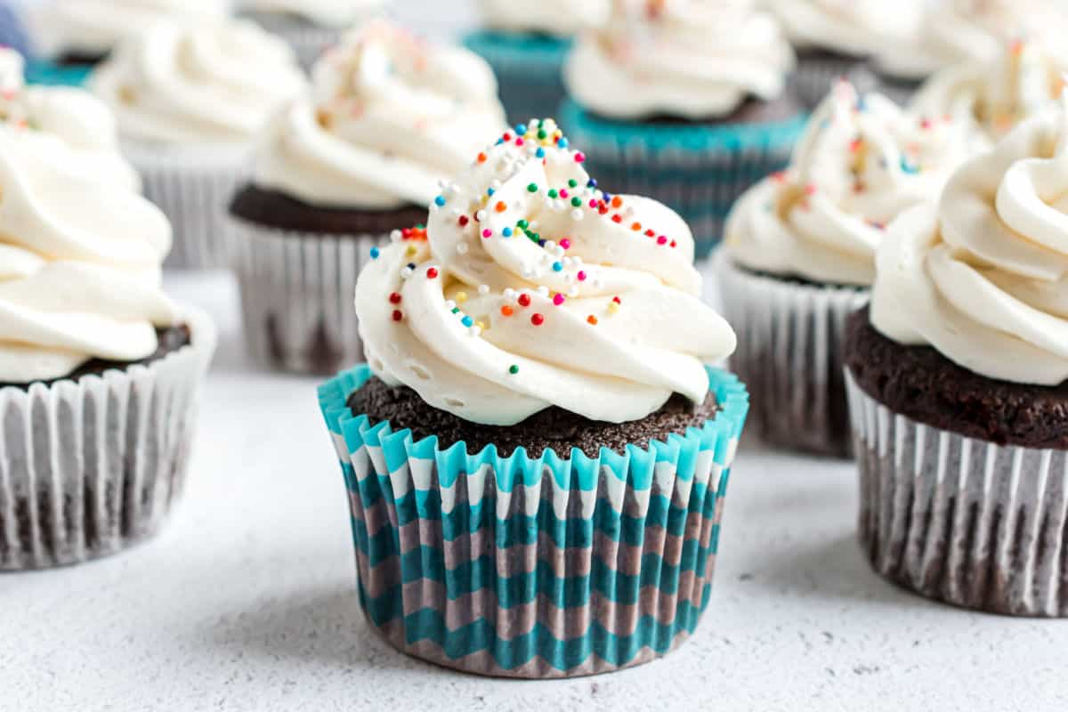Vanilla frosting on chocolate cupcakes with colorful non pariels.