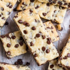 Chocolate chip shortbread bars stacked on parchment paper.