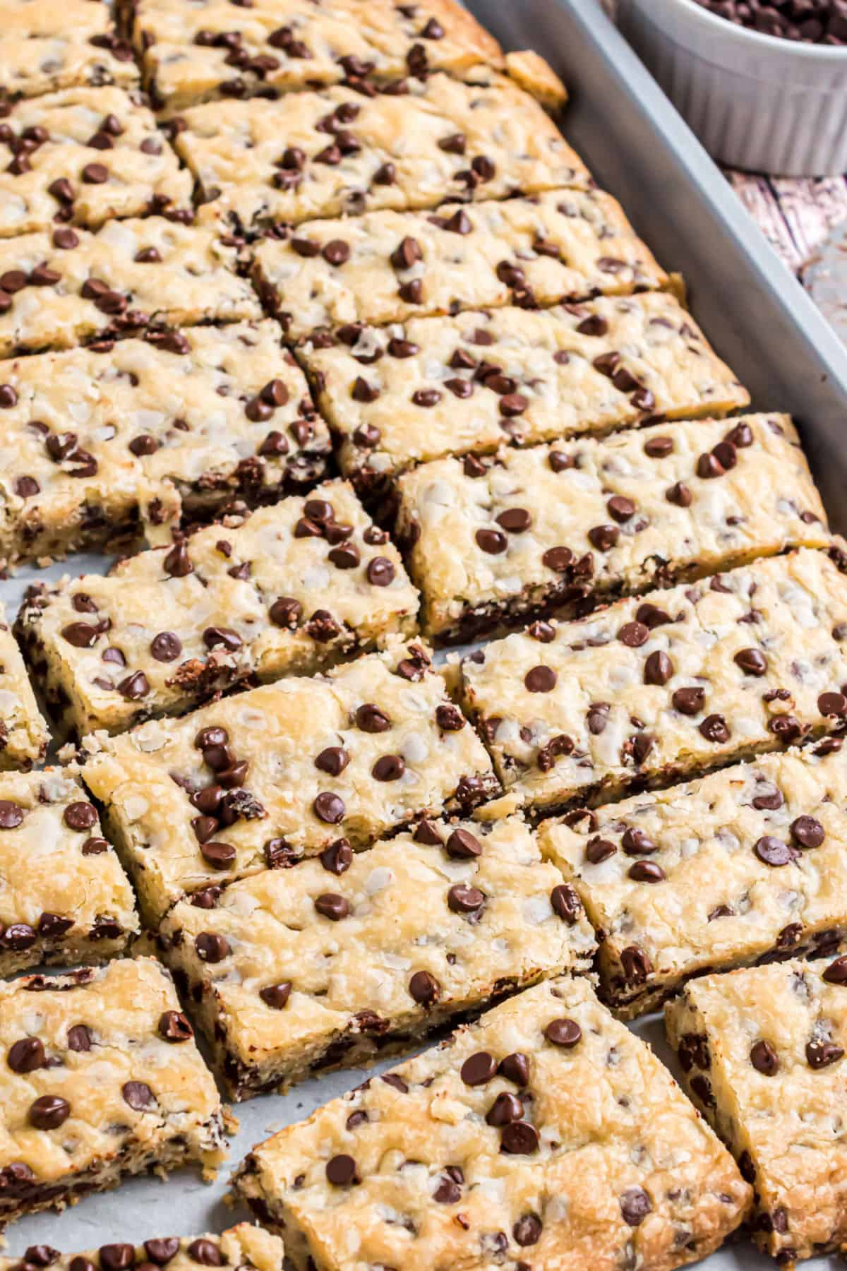 Rectangle shortbread cookies with chocolate chips on a baking sheet.