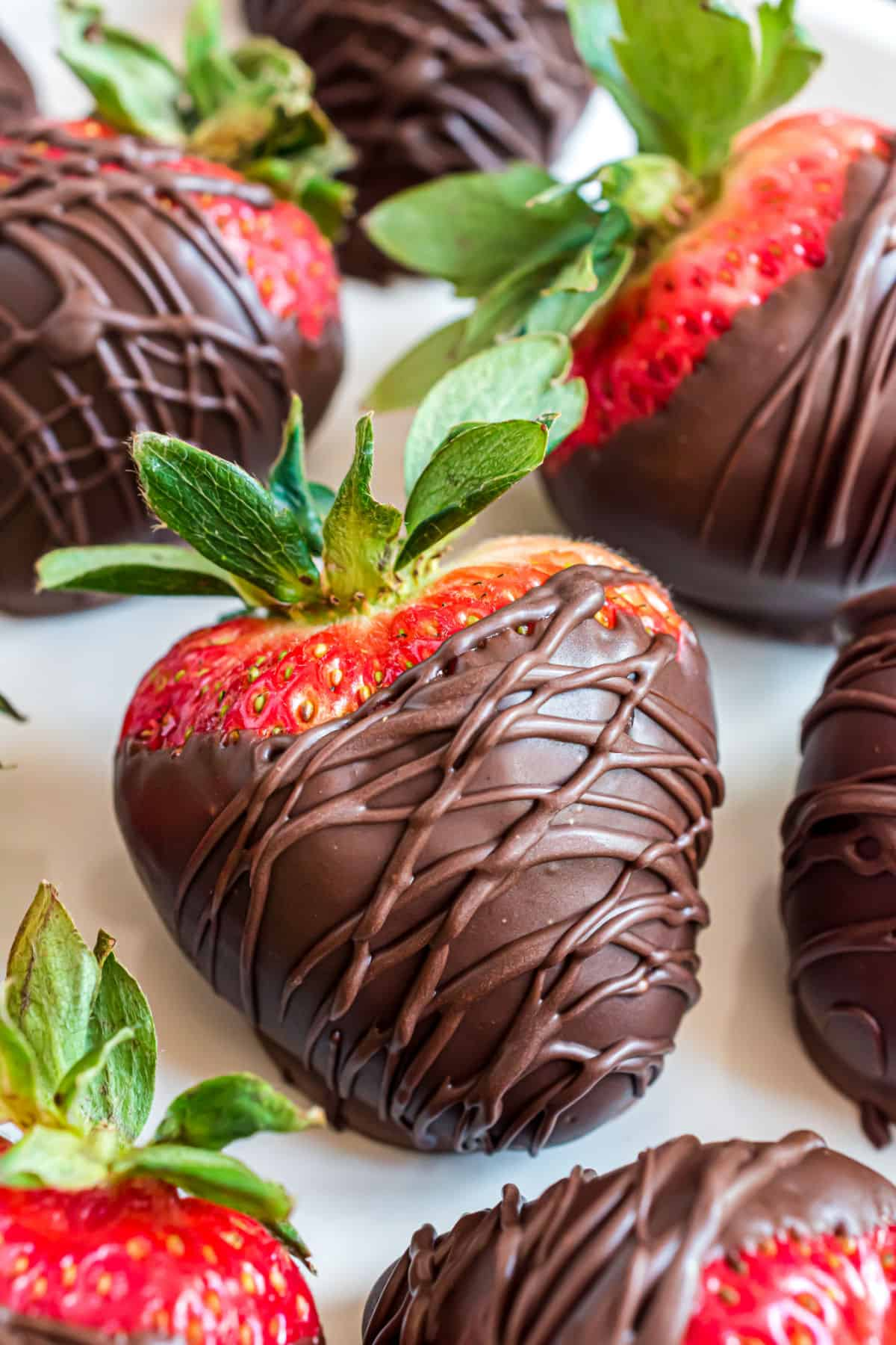 Chocolate covered strawberries on a piece of parchment paper.