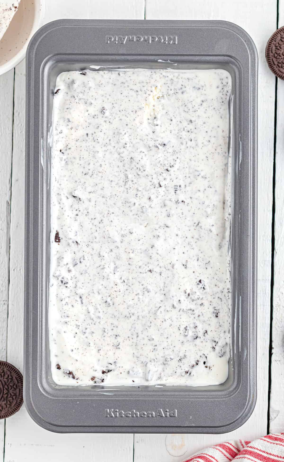 Metal loaf pan with cookies and cream ice cream.