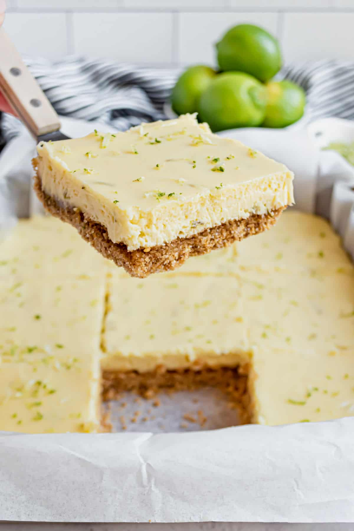 Key lime pie bar on a spatula for serving.