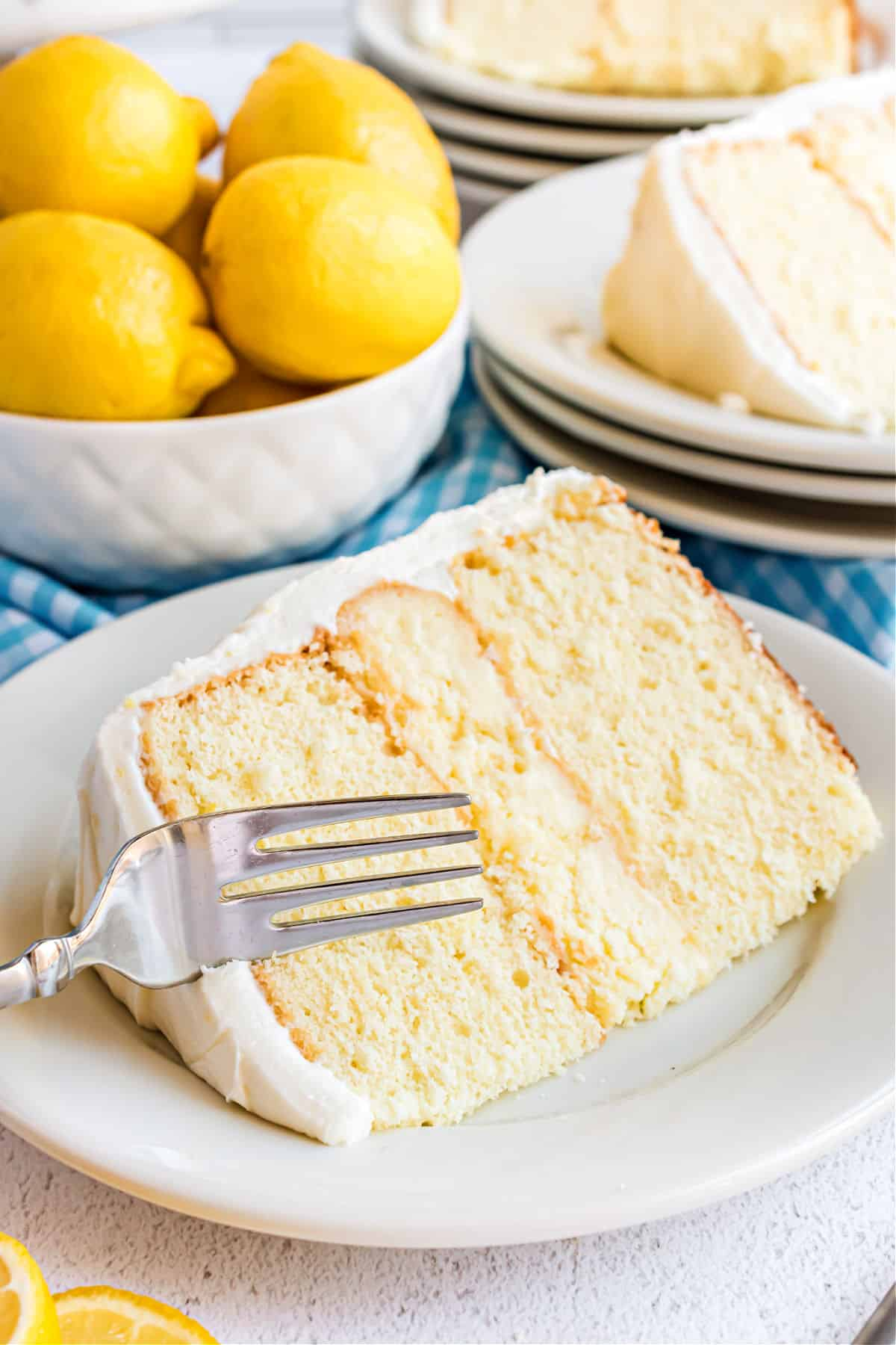 Slice of lemon cheesecake cake on a white plate with a fork.