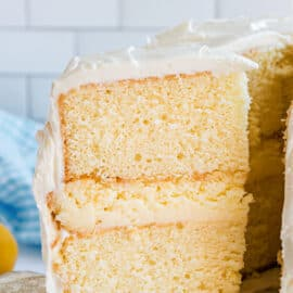 Slice of cake with two layers of lemon cake, cheesecake filling, and covered in frosting.