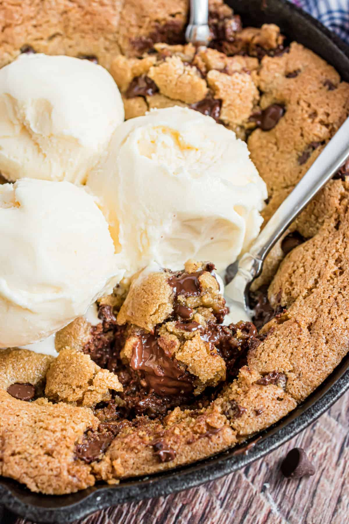 Gooey skillet cookie with spoons and ice cream.