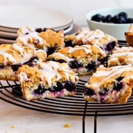Blueberry sugar cookie bars with cheesecake filling on wire rack.