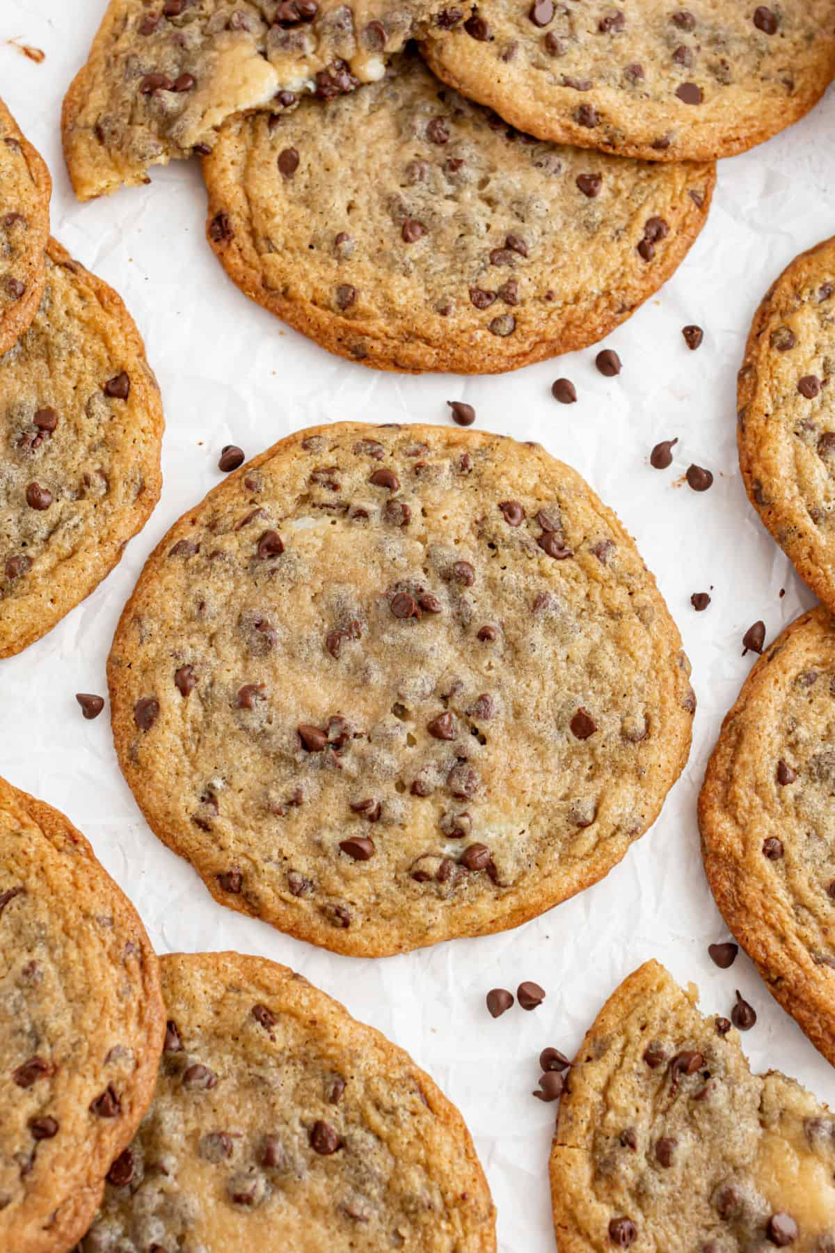 Chocolate chip cheesecake cookies on parchment paper.
