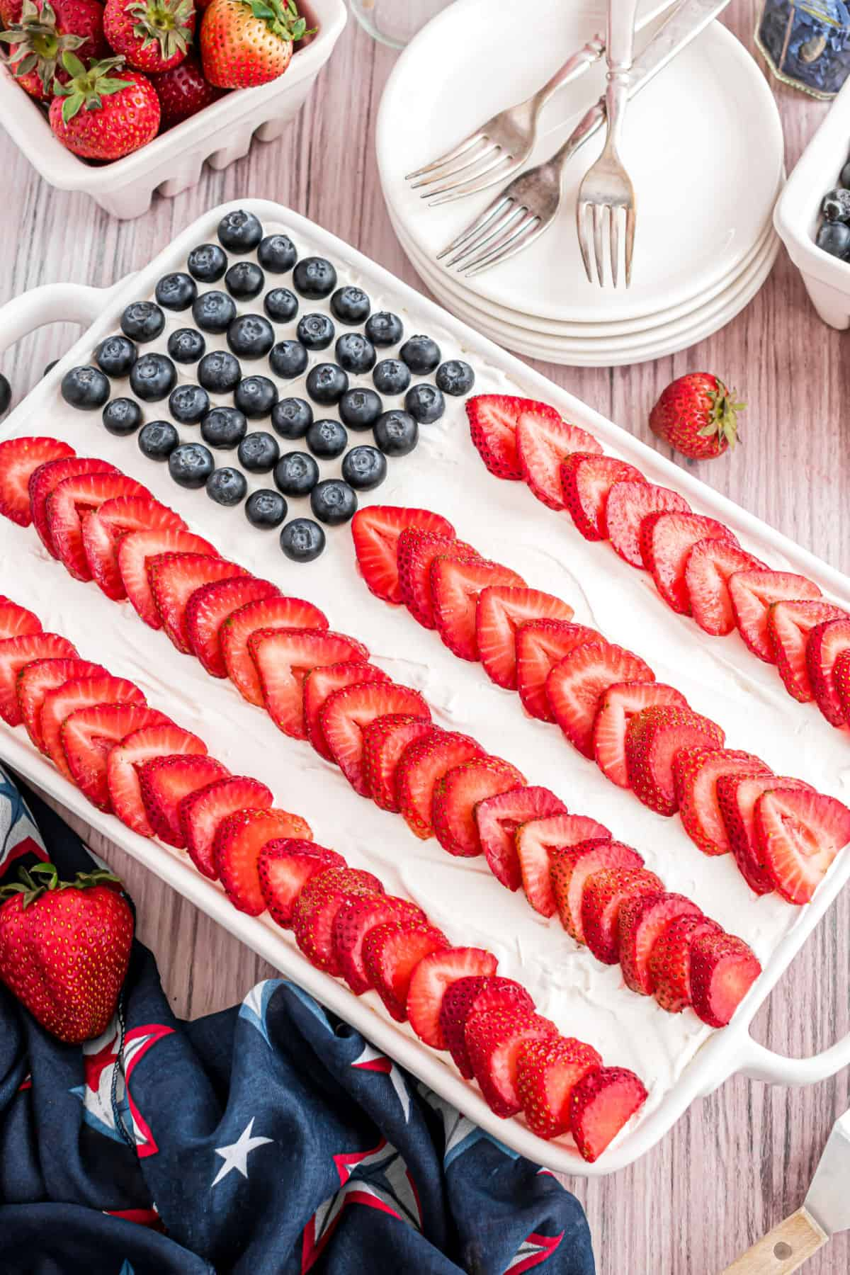 Red white and blue flag cake using whipped cream, blueberries, and strawberry slices.