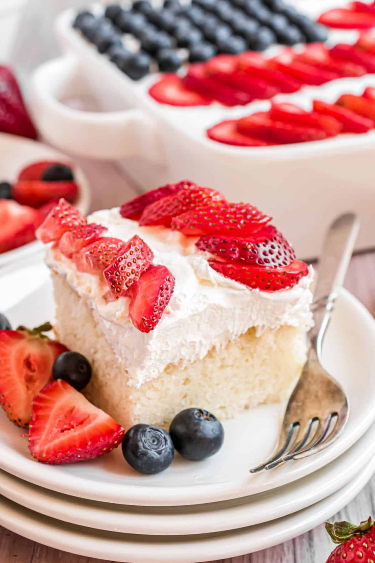 Slice of white cake with whipped cream and berries to resemble a flag.
