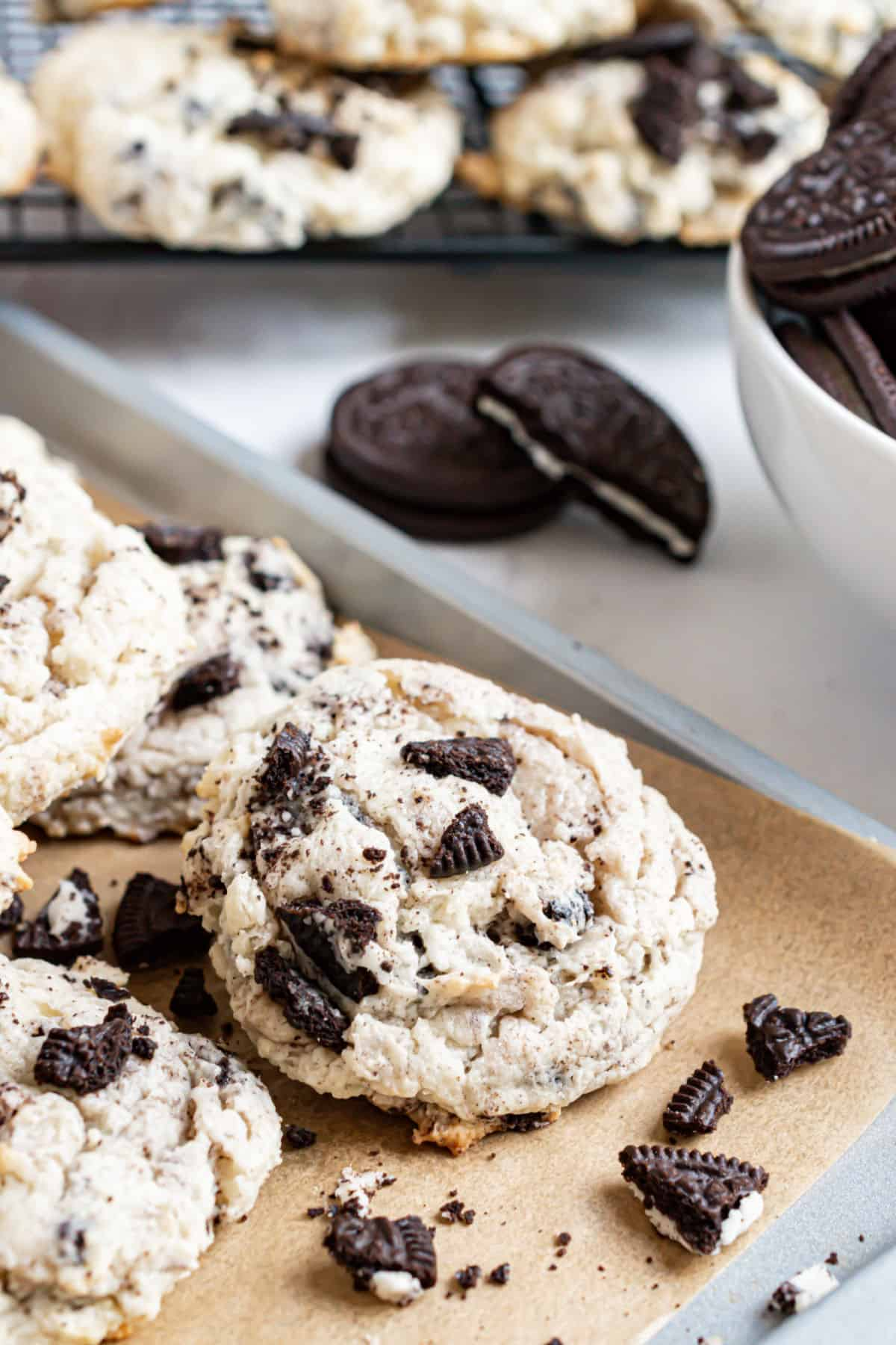 Oreo cookies stacked on parchment paper lined cookie sheet.