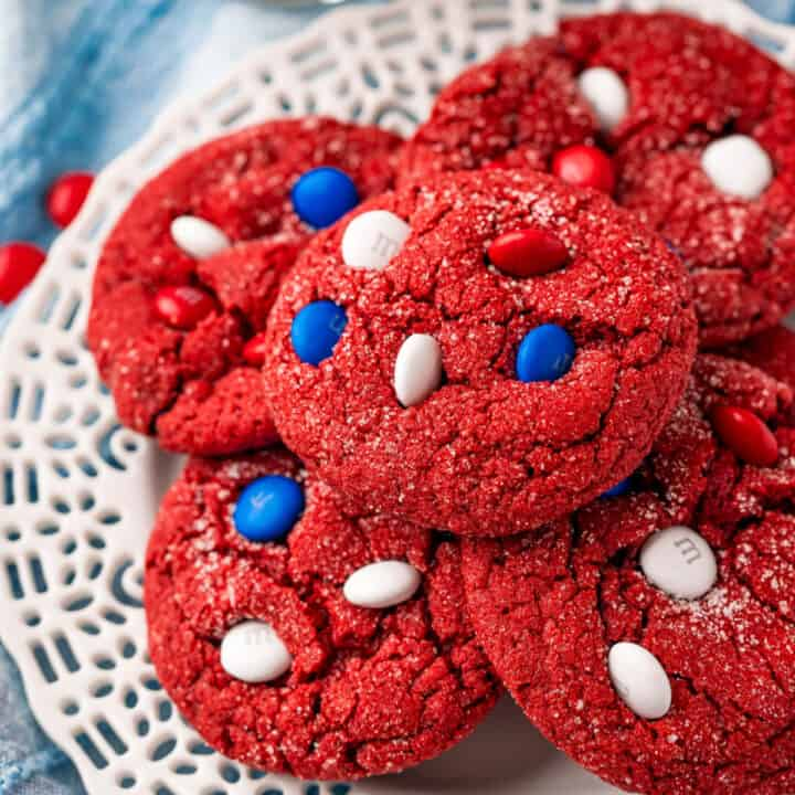 Red velvet cookies stacked on a white plate.
