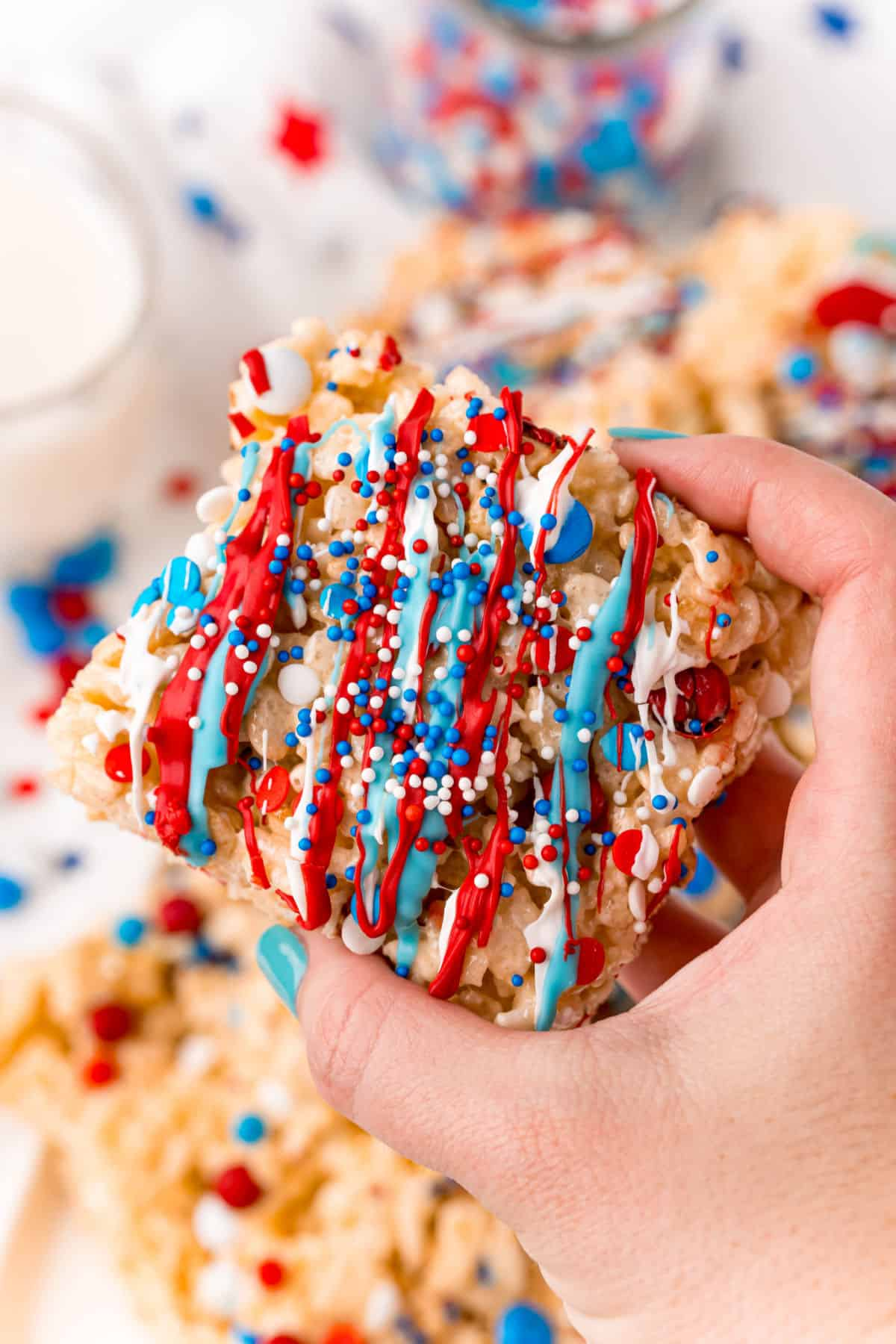 Red white and blue sprinkled rice crispy treat being held up close.