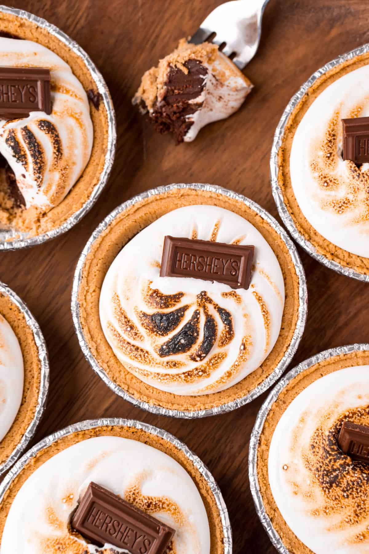 Mini s'mores pies with toasted marshmallow and chocolate bars on top.