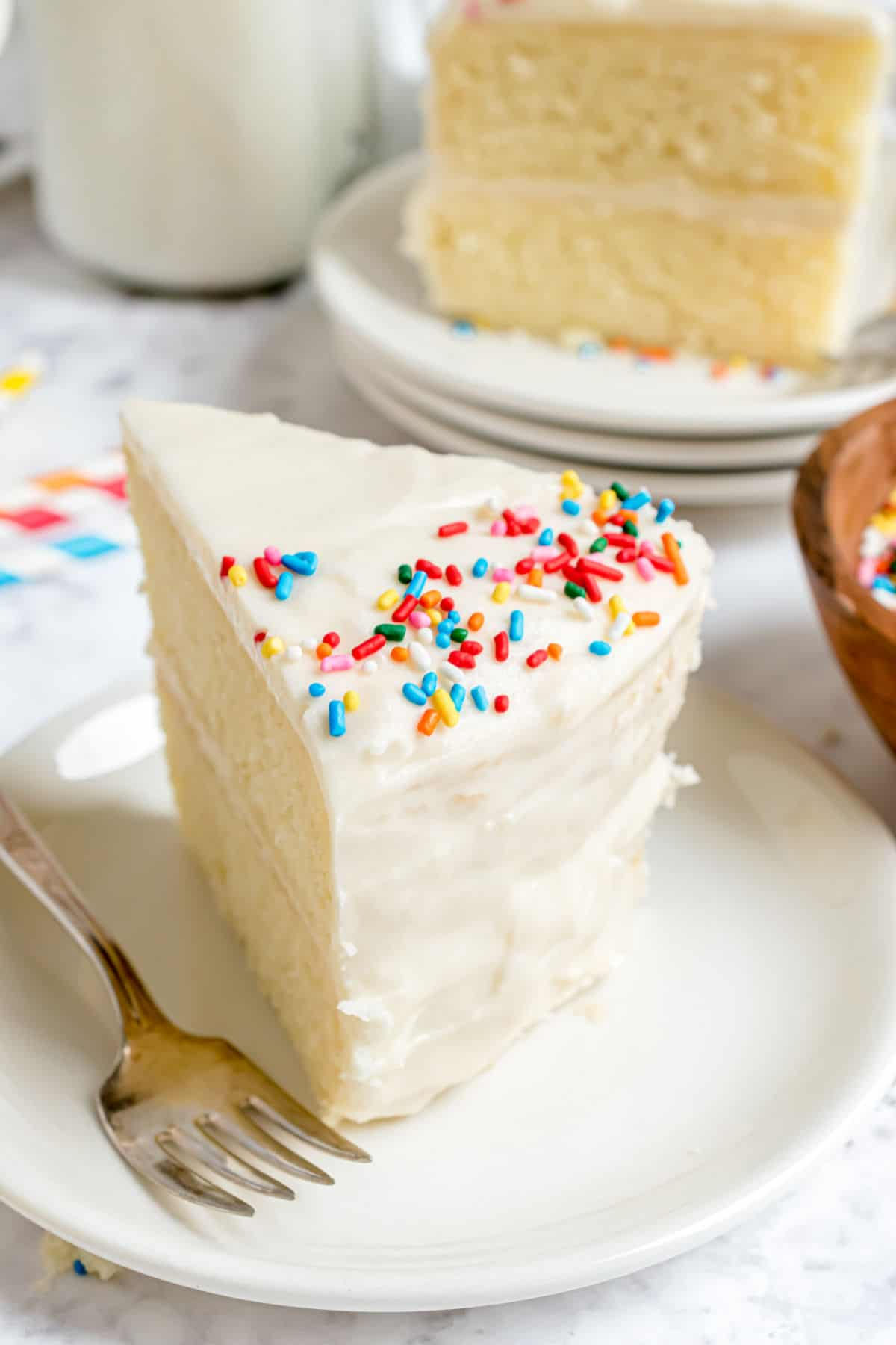 Vanilla sour cream frosting on a slice of cake with sprinkles.