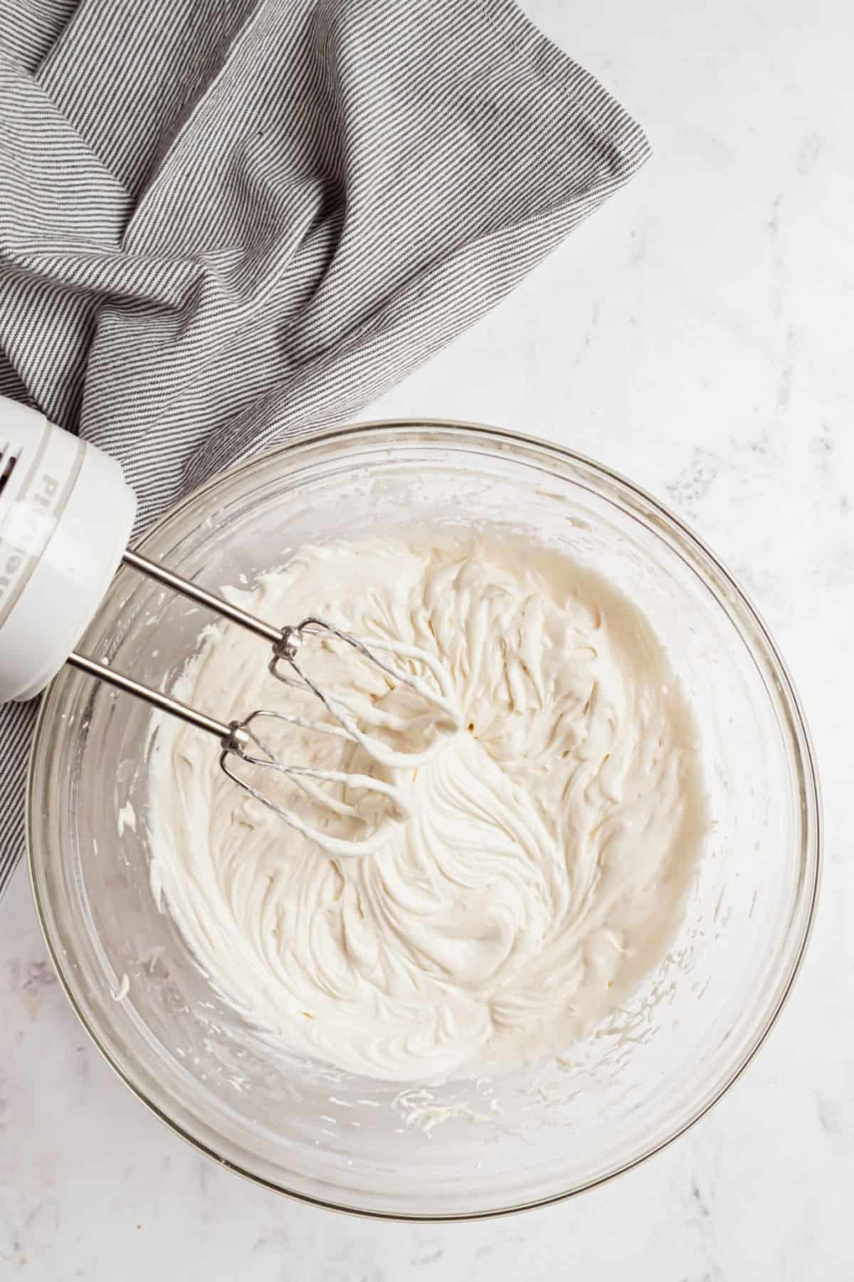 Sour cream frosting in mixing bowl with hand mixer.