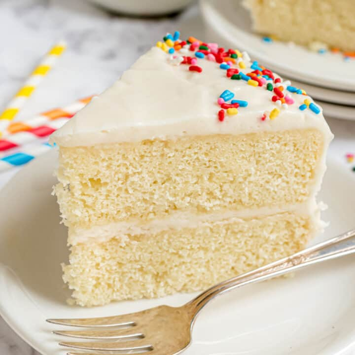 Slice of vanilla layer cake with vanilla sour cream frosting on white plate.