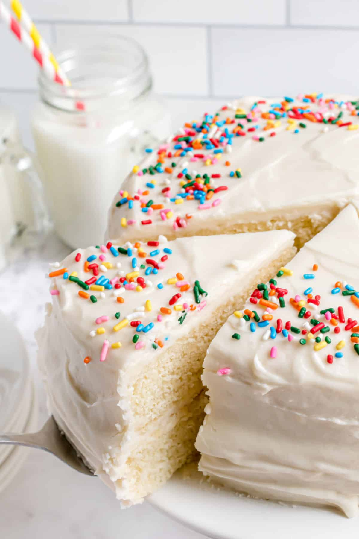 Vanilla layer cake with vanilla frosting and sprinkles.