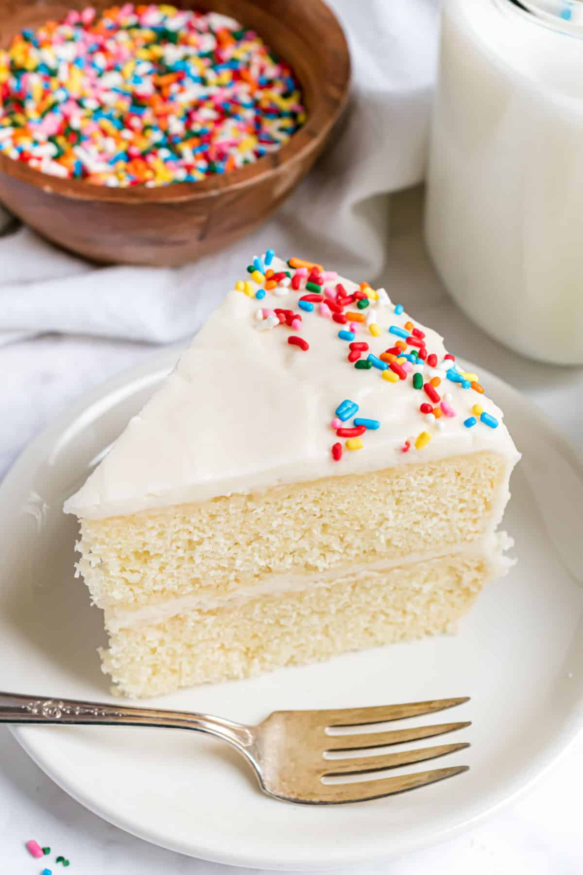 Slice of vanilla cake with sour cream frosting and sprinkles on a white plate with fork.