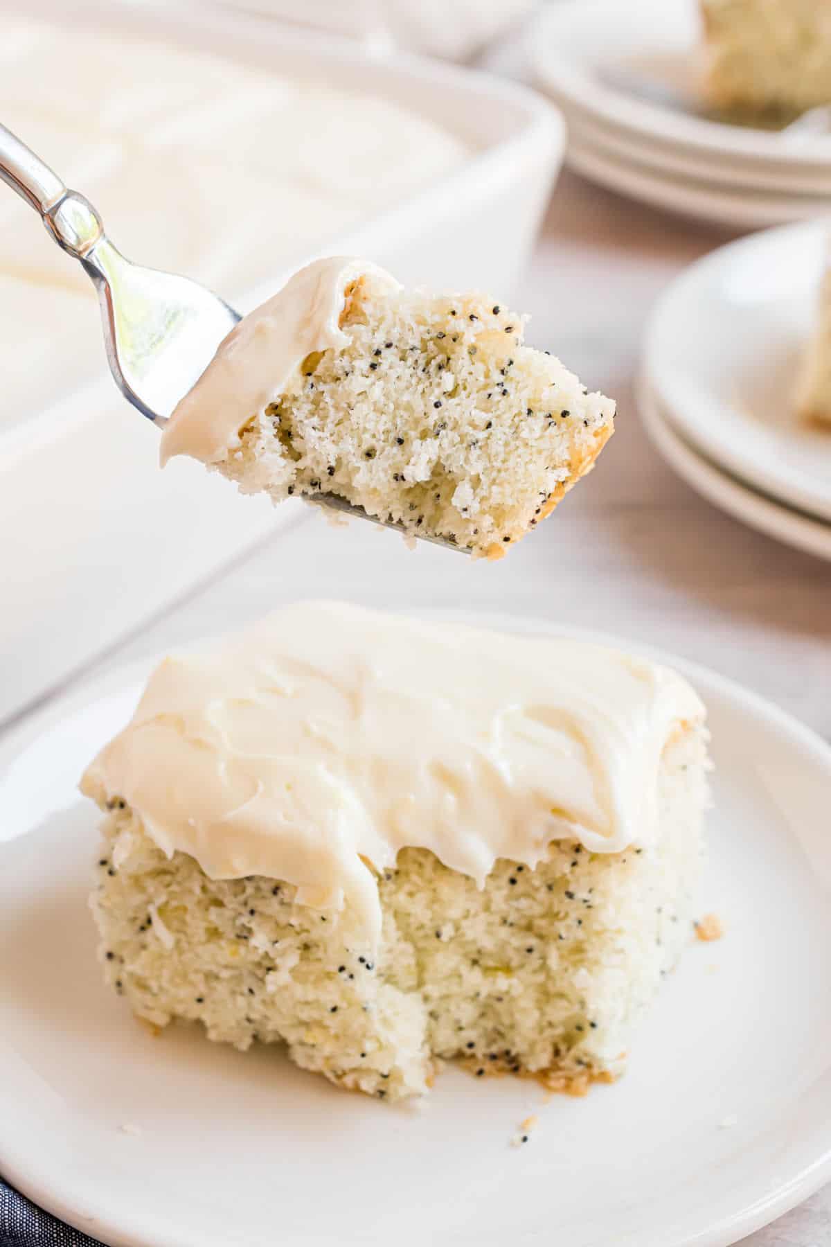 Forkful of lemon cake being taken from slice.
