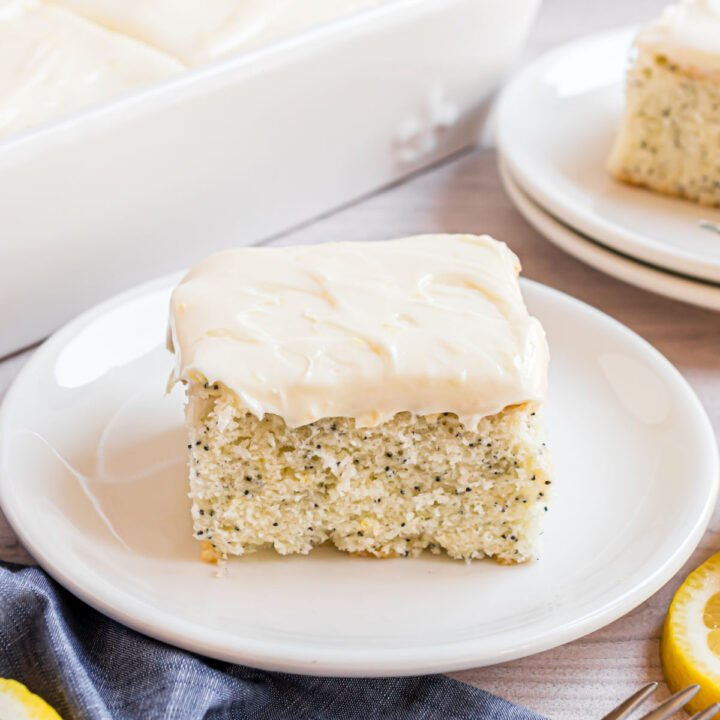Slice of lemon poppy seed cake with lemon cream cheese frosting on a white plate.